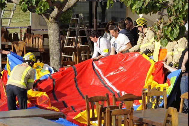 Varios operarios y bomberos retiran el castillo hinchable del restaurante Mas Oller, de Caldes de Malavella