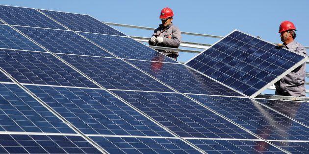 Unos trabajadores instalan paneles solares.