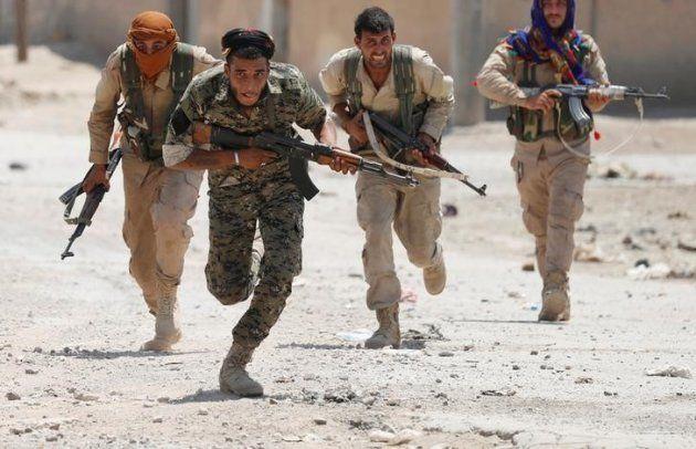 Combatientes kurdos corren por las calles de Raqqa (Siria), el pasado 3 de