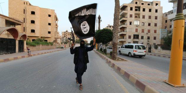 Un miembro del Estado Islámico enarbola su bandera en la ciudad siria de Raqqa, en junio de