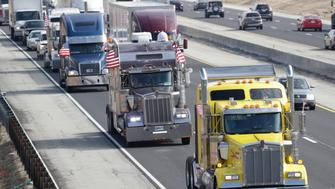 "Truckers participate in a ""slow roll"" protest on Interstate 465 in Indianapolis, Thursday, Feb. 21, 2019. Hundreds of truck drivers drove two laps around Indianapolis on 465 to protest regulations implemented in 2017 to force truck drivers to use an electronic logging device to track their hours on the road. (AP Photo/Michael Conroy)"