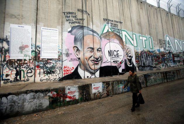 Una mujer pasa ante una pintada del primer ministro de Israel, Benjamin Netanyahu, en el muro de Belén....