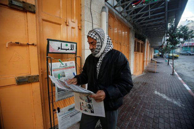 Un hombre lee la prensa -lo único expuesto en una ciudad cerrada por la huelga general- en la ciudad...