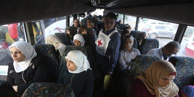 Un trabajador palestino de la Cruz Roja Internacional ayuda a los familiares de presos que esperan a...