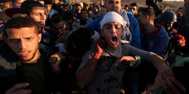 Un palestino herido es trasladado por otros manifestantes tras concentrarse ante soldados de Israel en...
