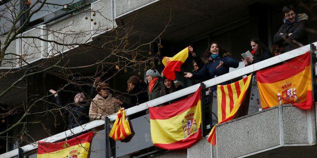 Varias personas sacan banderas de España y de Cataluña a su balcón en