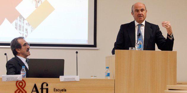 El ministro de Economía, Luis De Guindos, bajo la atenta mirada del presidente de Analistas Financieros...