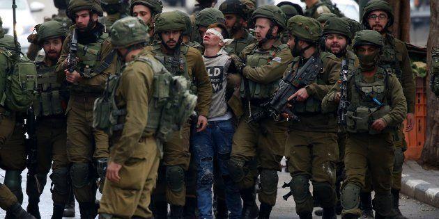 Un grupo de soldados israelíes detienen a Fawzi al-Junaidi, el pasado viernes en las calles de