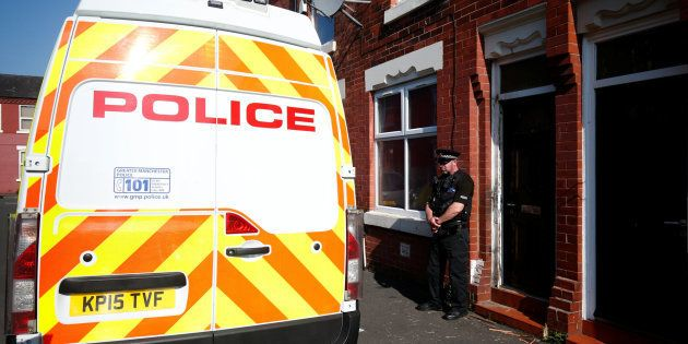 A police officer stand outside a property in Moss Side, following overnight raids in Manchester, Britain...