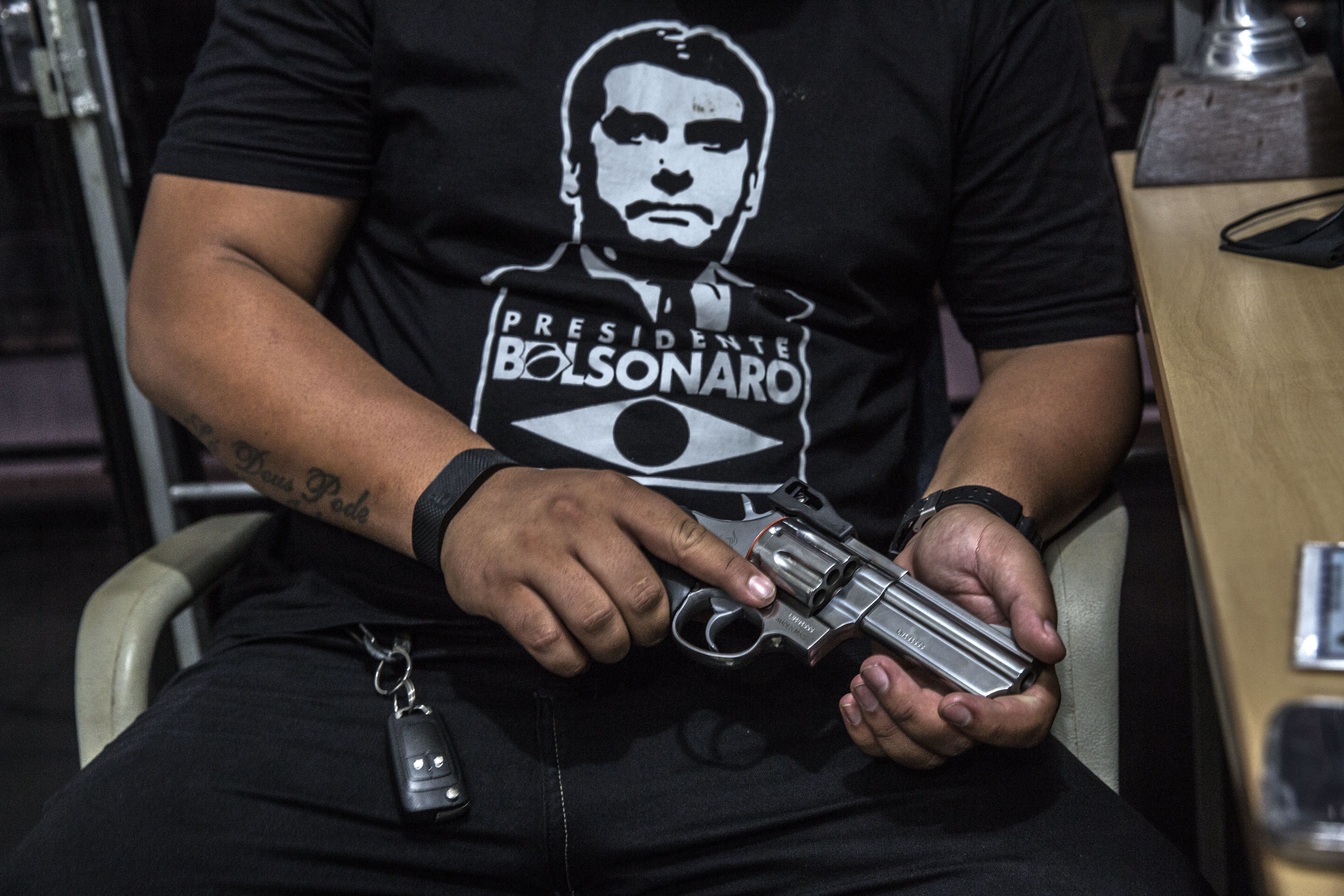A customer wearing a shirt in support of Jair Bolsonaro, Brazil's president, views a Forjas Taurus SA firearm for sale at a gun shop in Sao Joao do Meriti, Brazil, on Monday, Jan. 14, 2018. Bolsonaro signed a decree loosening the country's restrictive gun regulations, and hinted at further measures to arm law-abiding citizens to combat rampant crime. Photographer: Dado Galdieri/Bloomberg via Getty Images