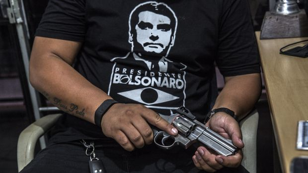 A customer wearing a shirt in support of Jair Bolsonaro, Brazil's president, views a Forjas Taurus SA firearm for sale at a gun shop in Sao Joao do Meriti, Brazil, on Monday, Jan. 14, 2018. Bolsonarosigned a decree loosening the country's restrictive gun regulations, and hinted at further measures to arm law-abiding citizens to combat rampant crime. Photographer: Dado Galdieri/Bloomberg via Getty Images