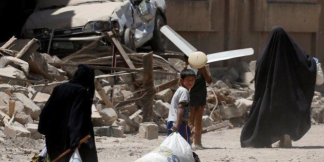 Civiles iraquíes escapan con algunas de sus pertenencias desde el oeste de Mosul, este
