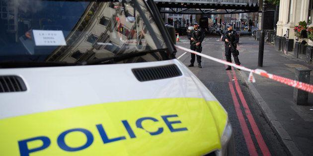 Dos agentes montan guardia cerca del lugar en el que se estrelló la camioneta del terrorista, en el puente...