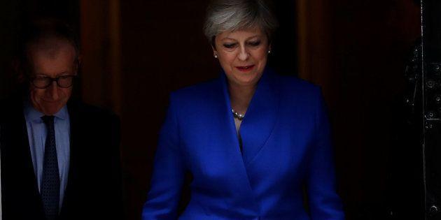 Theresa May, vestida de azul conservador, sale de la residencia oficial para ir a ver a la reina