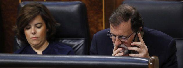 Rajoy habla por el móvil y la vicepresidenta mira al
