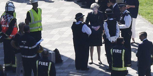 La primera ministra británica, Theresa May , conversa con agentes de la policía en el lugar del
