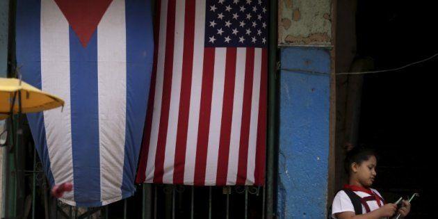 Una niña en uniforme escolar, ante una casa engalanada con las banderas de Cuba y EEUU en La Habana,...