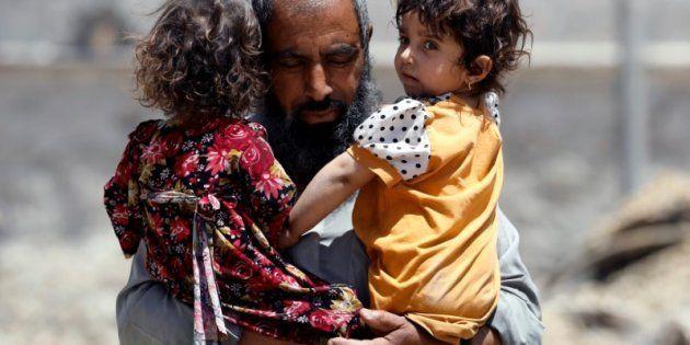 Un hombre trata de escapar de los choques en el oeste de Mosul cargado con dos