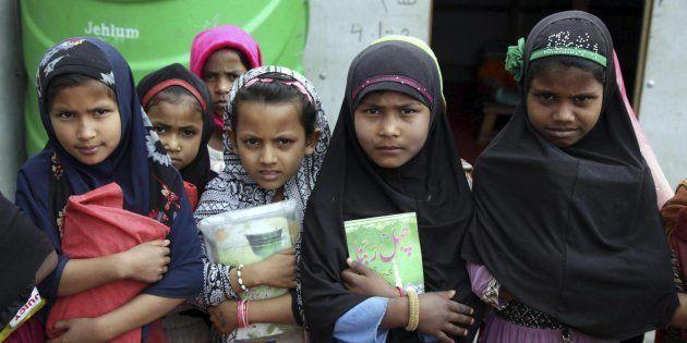 Niñas musulmanas de la etnia rohingya mientras sostienen sus libros religiosos en una madrasa, escuela...