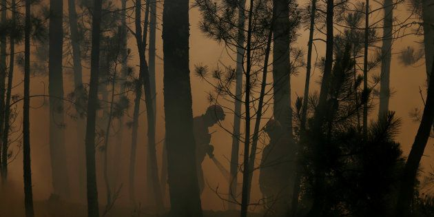 Una pareja de bomberos trata de controlar el fuego en Capelo, cerca de Gois, en la tarde de