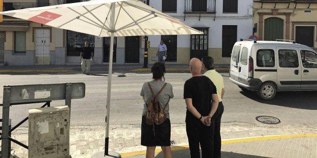 Un grupo de personas espera bajo una sombrilla a que se ponga en verde para peatones el semáforo en una...