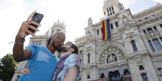 Una pareja se fotografía junto a la fachada del Ayuntamiento de Madrid, con la bandera del orgullo gay