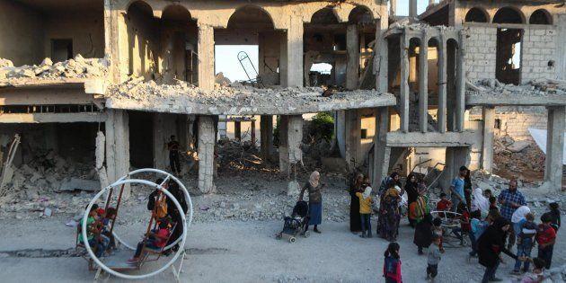 Un grupo de padres esperan a sus hijos mientras juegan en un columpio entre los escombros en