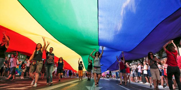 Varias personas portan una bandera gigante durante la manifestación del Orgullo de