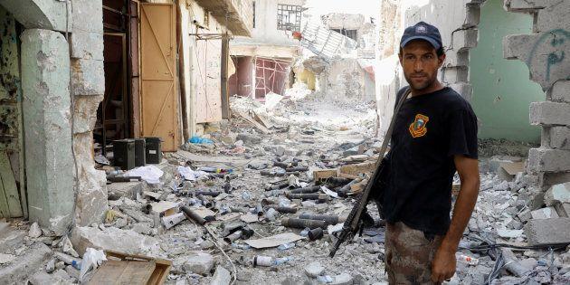 Un combatiente antiterrorista posa junto a los restos de artillería de un mortero en la ciudad vieja...