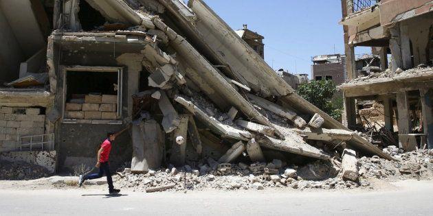 Un niño juega entre los restos de un edificio destrozado en