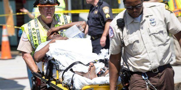 Una víctima herida es sacada de la escena en una camilla después del