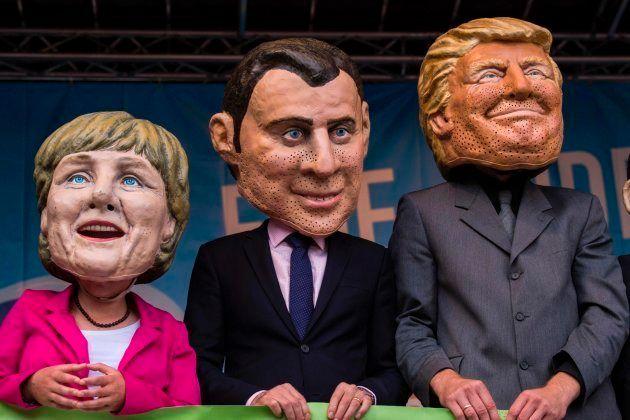 Manifestación en contra de los líderes del G20 con cabezudos de Merkel, Macron y