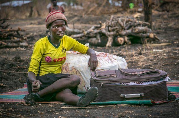 Una refugiada de Kajo Keju (Sudán del Sur) se sienta con su maleta en el campo de refugiados de Palorinya,