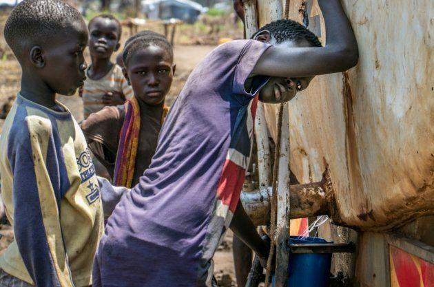 Niños recogiendo agua de uno de los camiones cisterna del campo de refugiados de Palorinya, en
