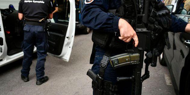 Un agente de policía, frente a su vehículo, en la edición número 104 del Tour de Francia. / AFP PHOTO...