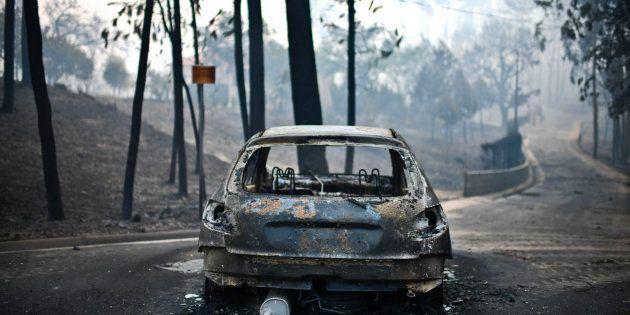 Fotografía tomada el 18 de junio de 2017 en la que se muestra un coche carbonizado en la carretera, tras...