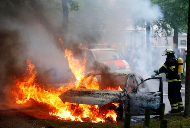 La policía acaba con el fuego de uno de los coches incendiados durante las protestas en
