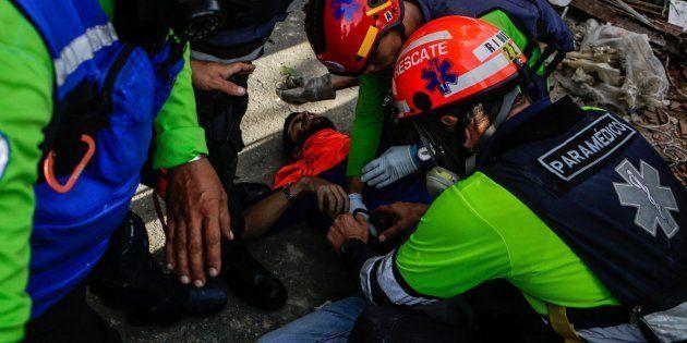 Personal médico auxilia a un manifestante herido durante las manifestaciones del lunes en