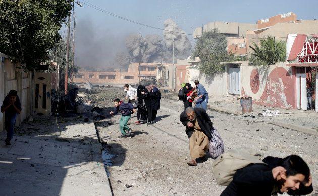 Un grupo de civiles corre en mitad de un bombardeo de la coalición contra supuestas posiciones del ISIS,...
