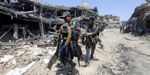 Miembros de la Policía Federal de Irak trasladan cinturones preparados por el ISIS para cometer atentados...
