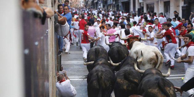 Los toros llegan a la curva de Mercaderes de Pamplona, durante el sexto encierro de los sanfermines de