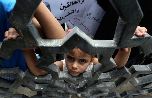 Una niña se asoma a la verja del paso fronterizo de Rafah, entre Gaza y Egipto, durante una protesta...