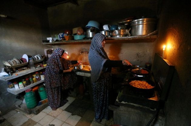 Unas mujeres palestinas cocinan durante un corte de luz en su casa del campo de refugiados de Khan