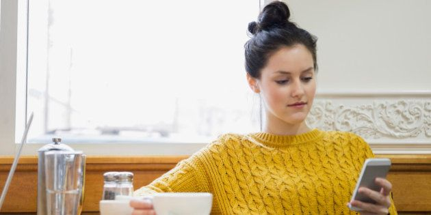 Woman texting and drinking cappuccino in