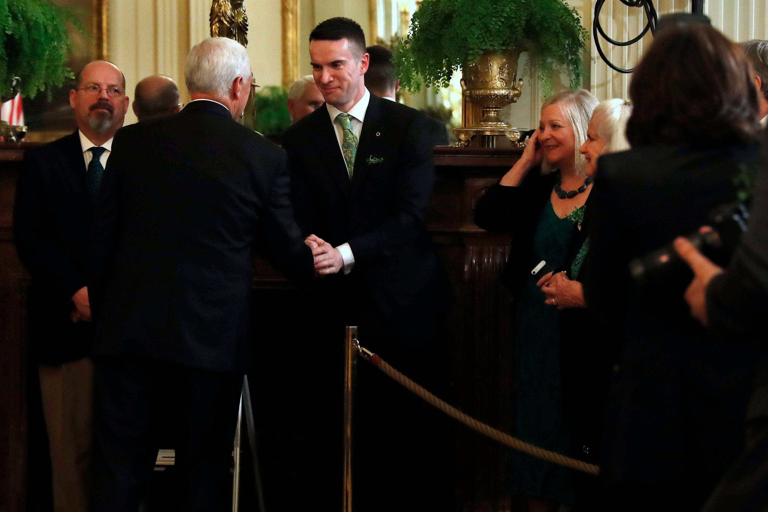 The partner of Irish Prime Minister Leo Varadkar, Matt Barrett, center, shakes hands with Vice President Mike Pence, Thursday, March 14, 2019, after the annual presentation of a bowl of shamrocks in the East Room of the White House in Washington. (AP Photo/Jacquelyn Martin)