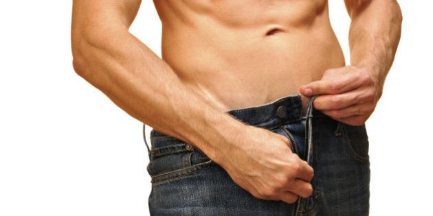 Sexy man with lean abdominals unzips his jeans on white