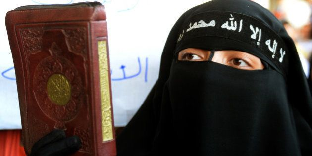 A fully veiled supporter of Egypt's toppled president Mohamed Morsi, holds a copy of the Koran, Islam's...