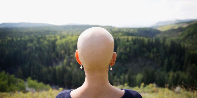 Female cancer survivor with shaved head looking at remote rural