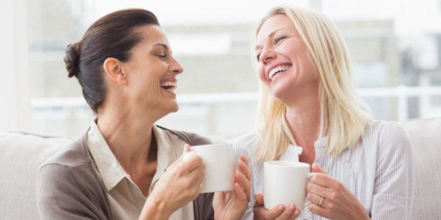 Cheerful women gossiping while having coffee in living