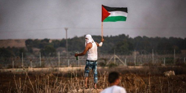 GAZA - OCTOBER 15: A Palestinian holds a Palestinian flag during clashes after Palestinians tried to...